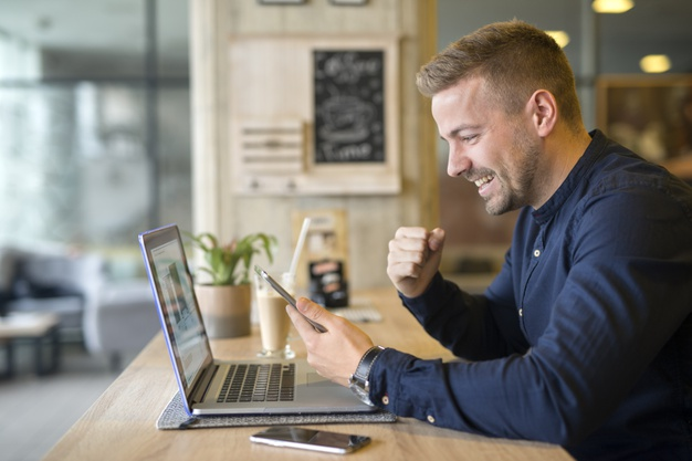 happy-freelancer-with-tablet-and-laptop-computer-in-coffee-shop_342744-942