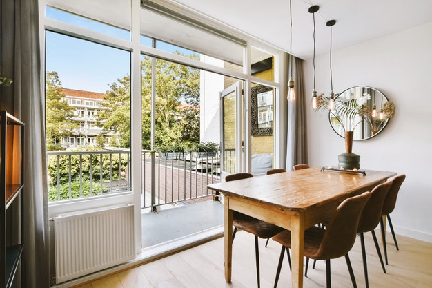 wooden-table-with-vase-and-chairs-placed-near-opened-balcony-door-in-light-dining-room-at-home_305343-110